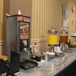 breakfast buffet set up with waffle machine and juice stations