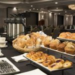 meeting room breakfast setup with pastries, coffee and bagels