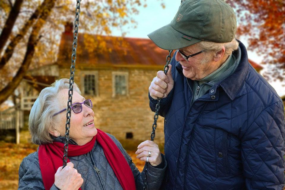 elderly couple on swing set